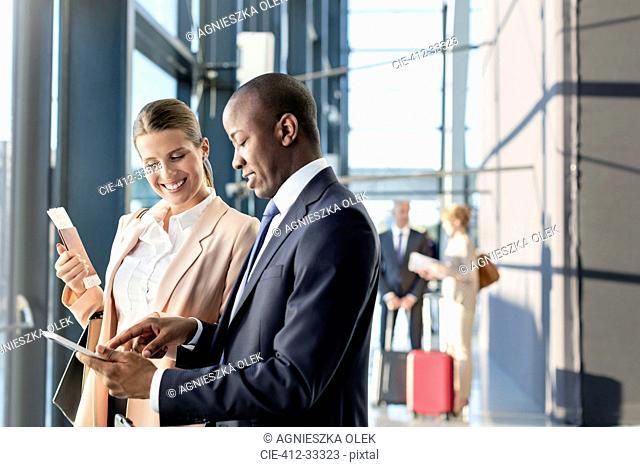 Business people using digital tablet in airport