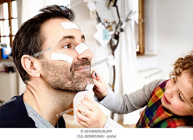 Girl sticking adhesive plaster onto father's chin