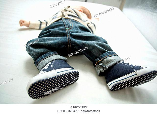 Closeup photo of baby boy feet in jeans and sneakers lying on bed