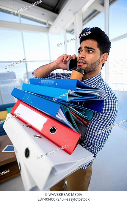 Male executive holding stack of files while talking on mobile phone