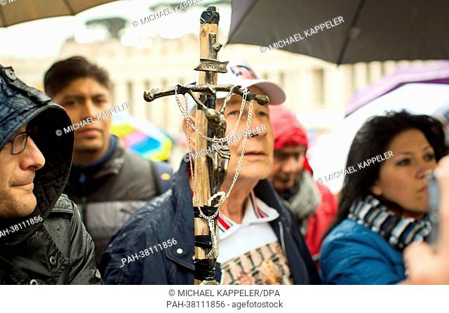 A pilgrim holds a crucifix and waits at St. Peter's Square for smoke to rise from the chimney of the Sistine Chapel in the Vatican, 13 March 2013