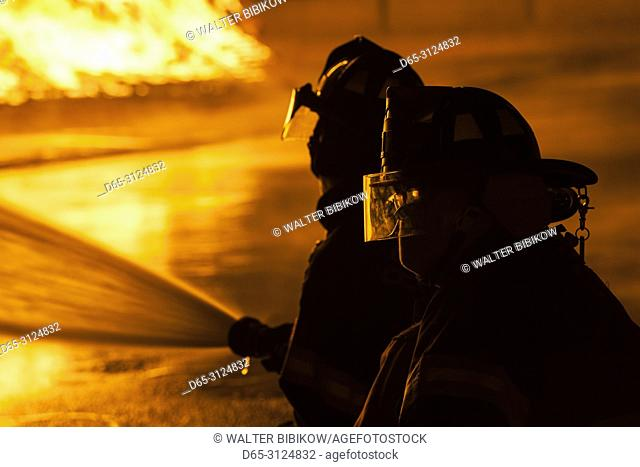 USA, New England, Massachusetts, Cape Ann, Rockport, Fourth of July Bonfire, silhouettes of firemen