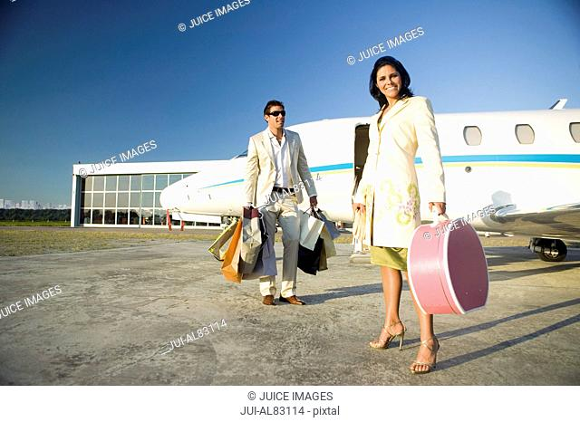 Couple with suitcases and shopping bags next to airplane