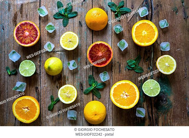 Sliced and whole lemons, oranges and limes, mint leaves and ice cubes on wood