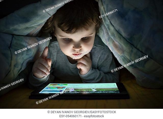 Little girl watching her tablet in the bed. Illuminated child face from device screen. Child dressed with pajamas under the covers hold a tablet