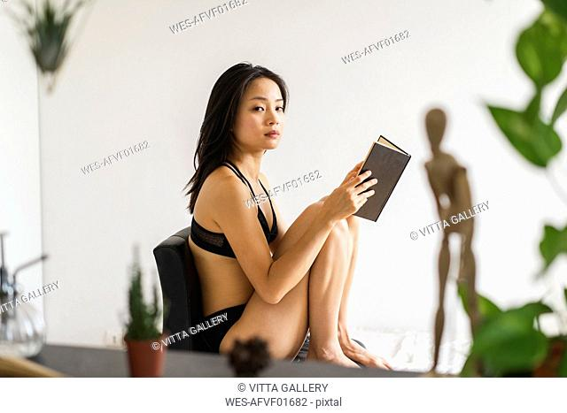 Portrait of attractive young woman in lingerie sitting on chair at home reading book