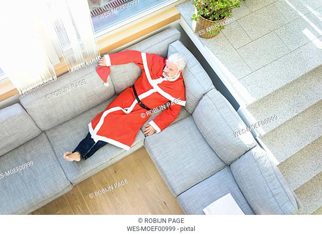 Bearded mature man wearing Santa costume lying on couch in living room