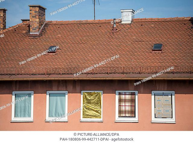 06 August 2018, Germany, Munich: The windows of a residential house are covered with blankets, curtains, cardboard boxes and a reflective emergency blanket