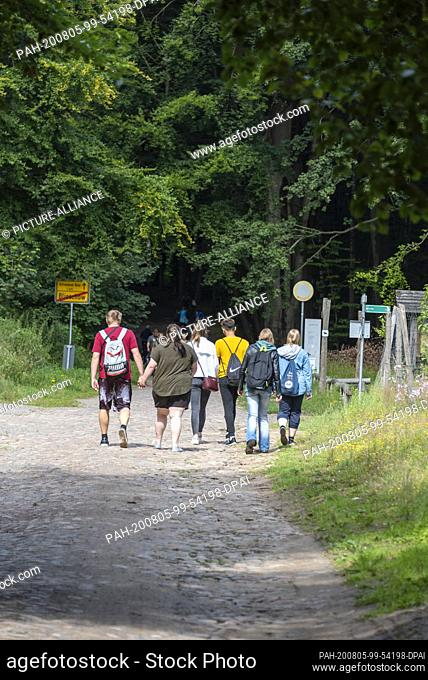 03 August 2020, Mecklenburg-Western Pomerania, Binz: Young holidaymakers walk from the small village of Blieschow to the Granitz hunting lodge