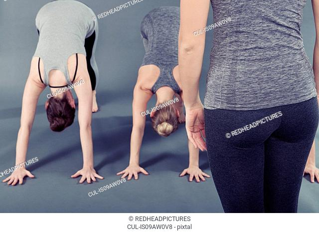 Young women practising yoga, grey background