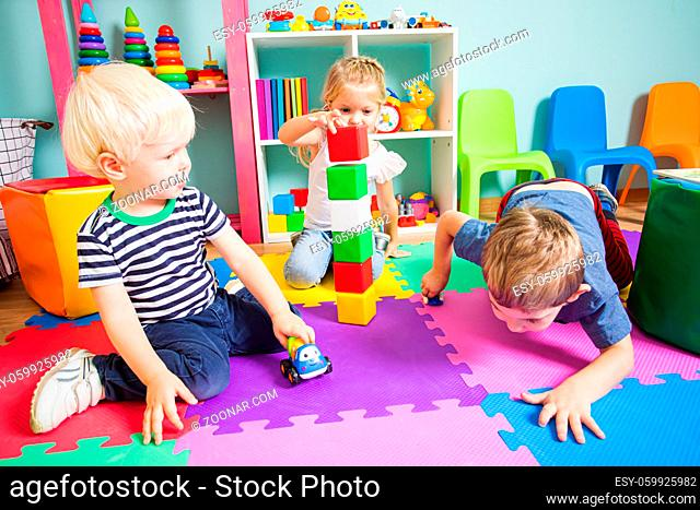 The toddler boys are playing with a toy cars on the floor in the playroom. Next to a little girl stacks on each other a colorful cubes