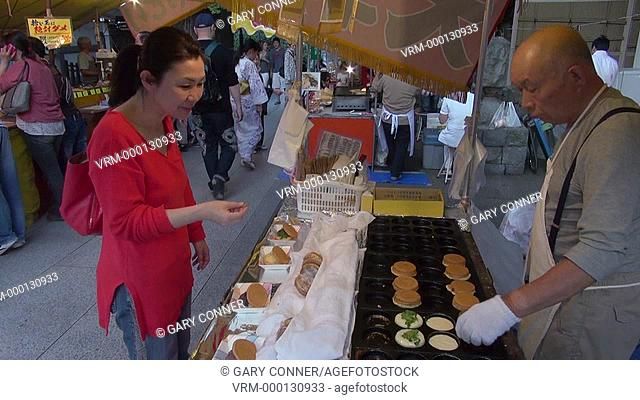 Woman buying sweets at Yushima Tenjin festival. Tokyo, Japan