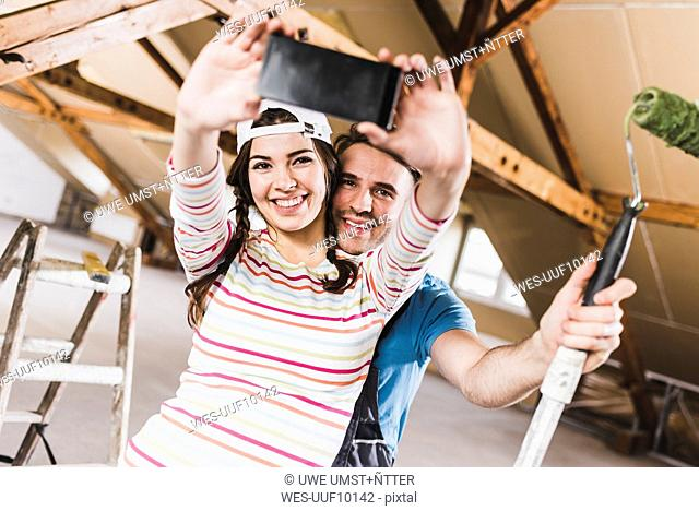 Young couple renovating their new home, taking smart phone selfies
