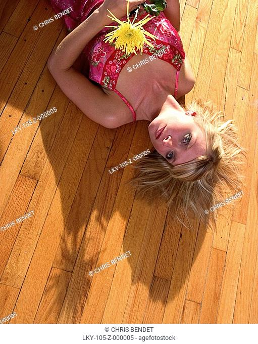 Young woman laying on floor, holding flower