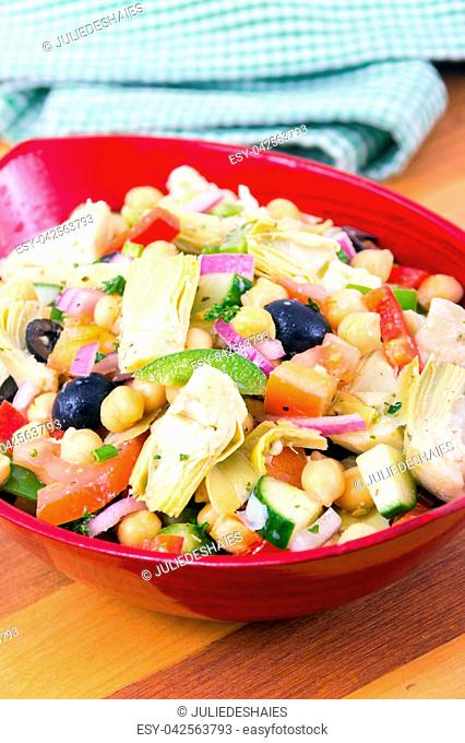 mixed Mediterranean salad bowl with artichoke and chick peas over wood table