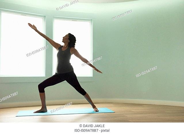 Mature woman doing yoga warrior pose in curved room