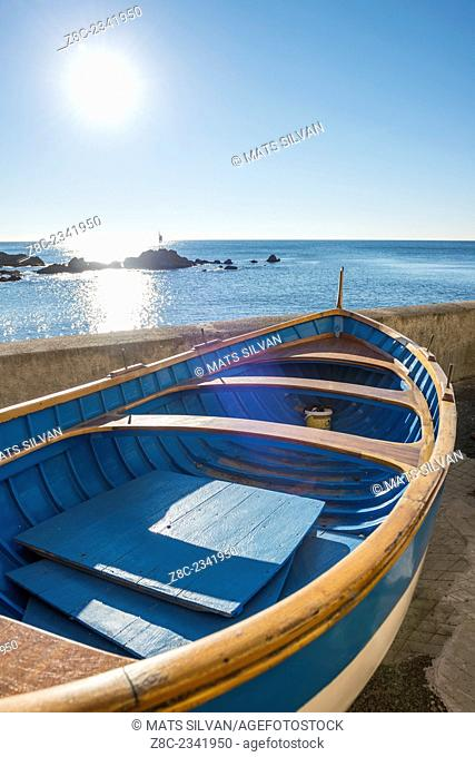 Old boat on the beach with sunshine in a sunny day with blue sky on the seacoast in Liguria, Italy