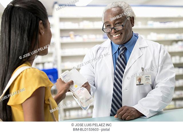 Black pharmacist handing medication to customer