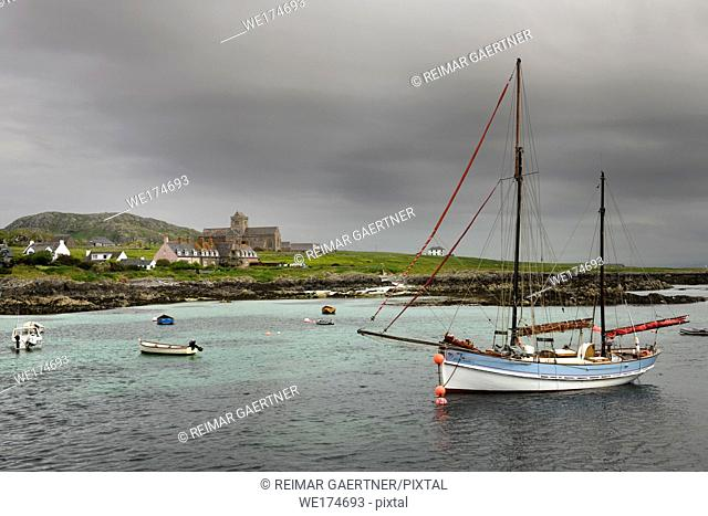 Iona Abbey at Baile Mor village on Isle of Iona in morning cloud with sailboat on Sound of Iona Inner Hebrides Scotland UK