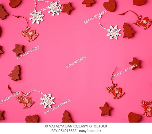 wooden carved Christmas decorations for the holiday tree on a pink background