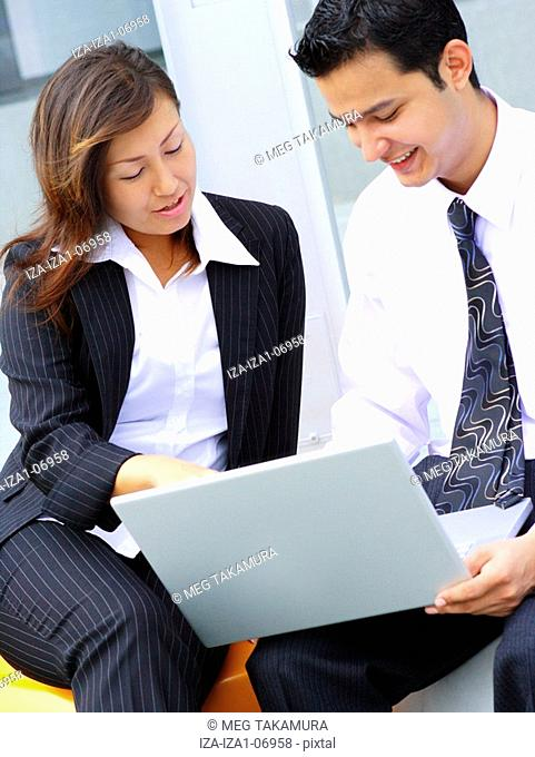 Businessman and a businesswoman sitting together and using a laptop