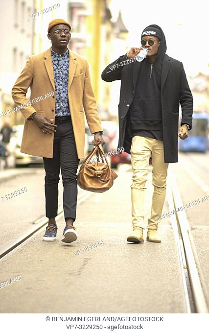 two fashionable men walking on street in city, streetstyle fashion clothes, Munich, Germany