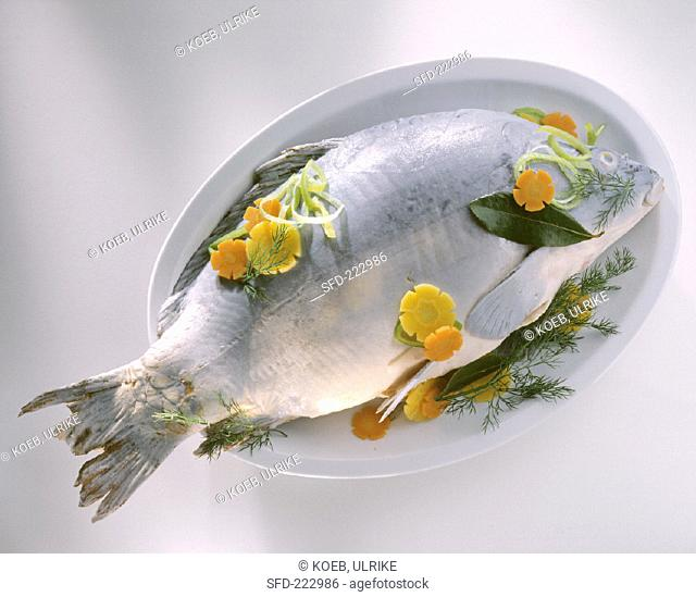 Carp cooked blue on a platter with vegetables and herbs