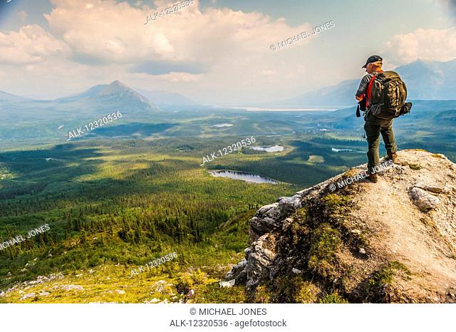 Backpacker overlooks scenic view from a bluff high above, Wrangell-St. Elias National Park, Southcentral Alaska, USA