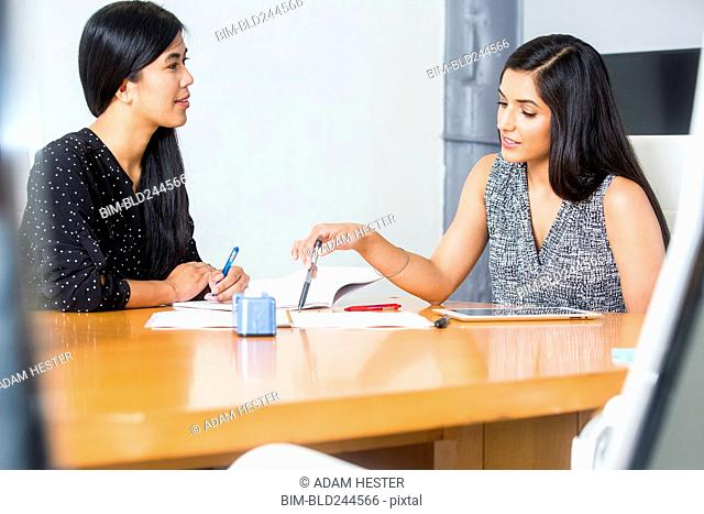 Women reading paperwork at table