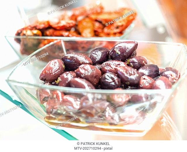 Black Greek styled olives and dried tomatoes in glass bowl
