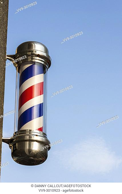 Traditional red and white barbers pole outside a hairdressers shop