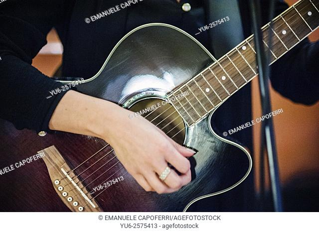 Hand of a woman with a ring while he plays guitar