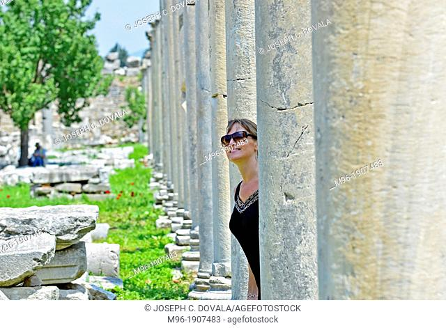 Woman tourist looks out from marble pillars at Ephesus, Turkey