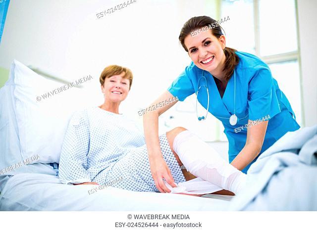 Nurse bandaging leg of patient