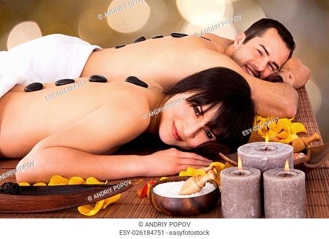 Beautiful Young Couple Enjoying Hot Stone Therapy In Spa Centre