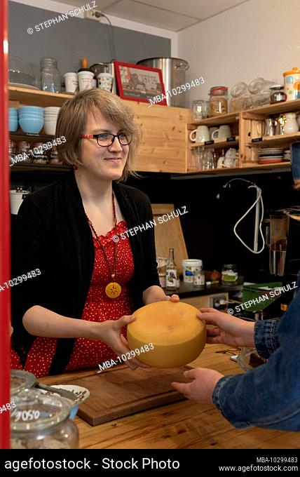 The owner of an unwrapped shop gives a customer a cheese