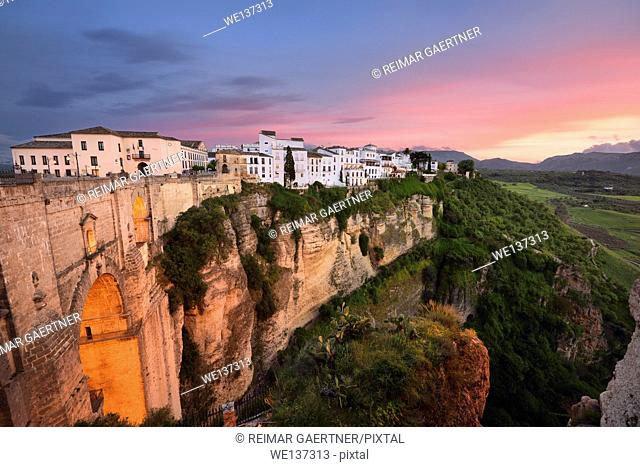 Red sky evening light on white buildings and orange cliffs at El Tajo Gorge Ronda Spain