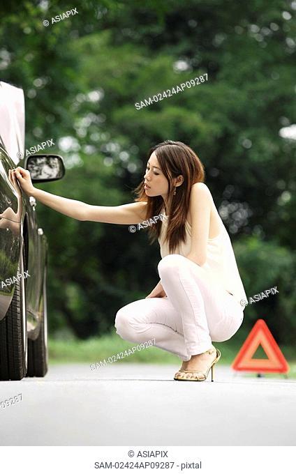 Woman inspecting car