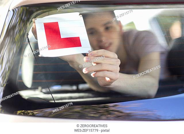 Learner driver placing letter L on rear window of car