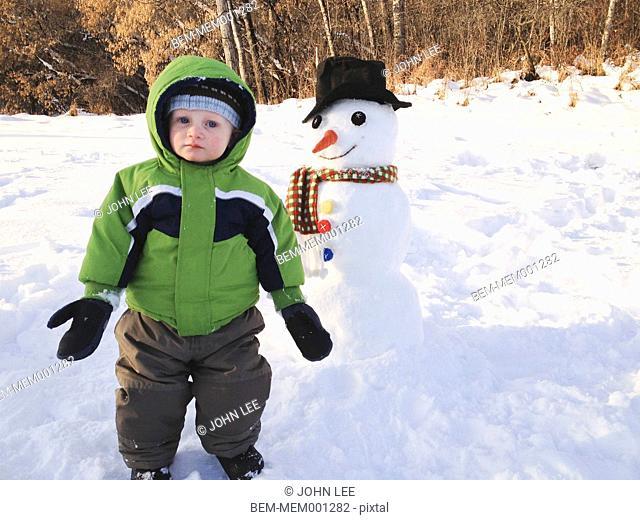 Boy building snowman outdoors
