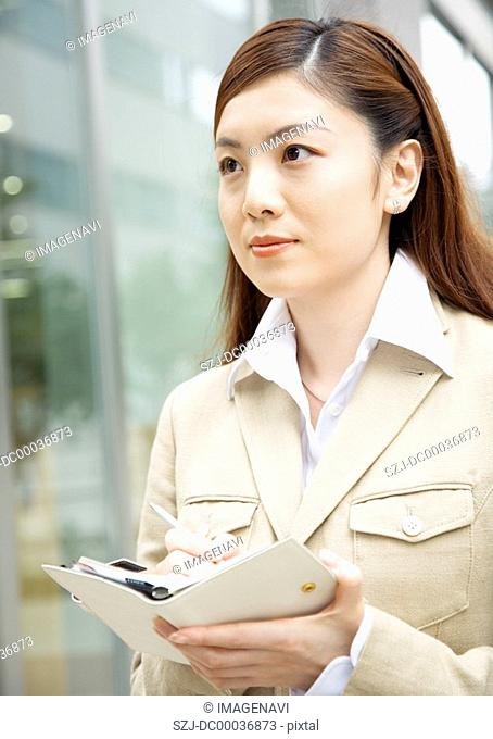 A woman journalist taking a note