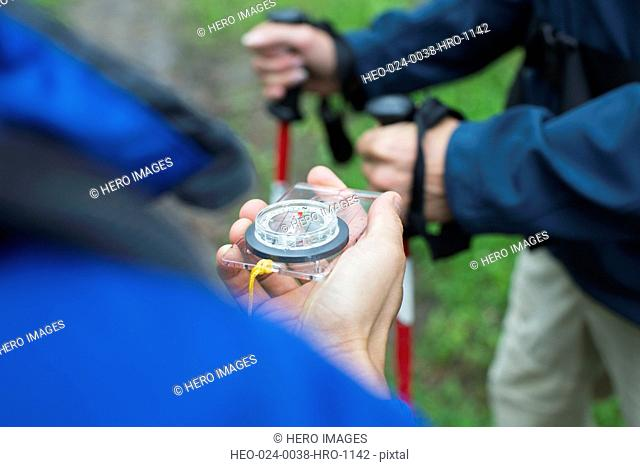 hikers checking direction with compass