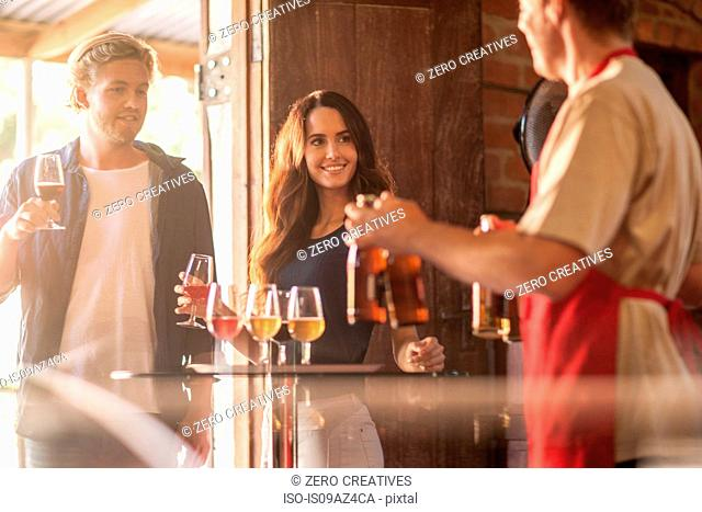 Couple and waiter in public house