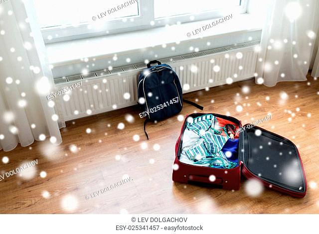 vacation, travel, tourism and objects concept - close up of bag with beach clothes and backpack on floor at home or hotel room