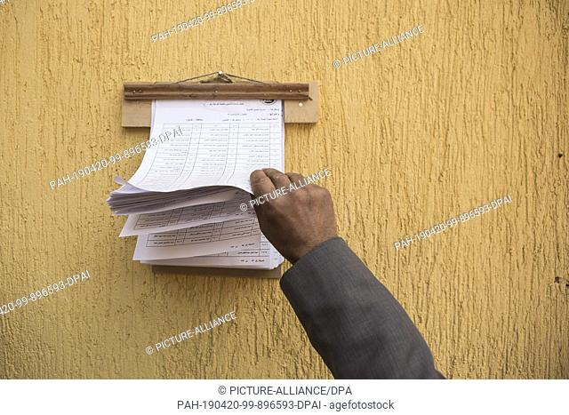 20 April 2019, Egypt, Cairo: A man searches for his polling station in the first day of the national referendum on the constitutional amendments extending the...