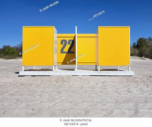 Yellow dressing cabin, changing cubicle number 22 on empty Pärnu beach in Estonia. Changing room