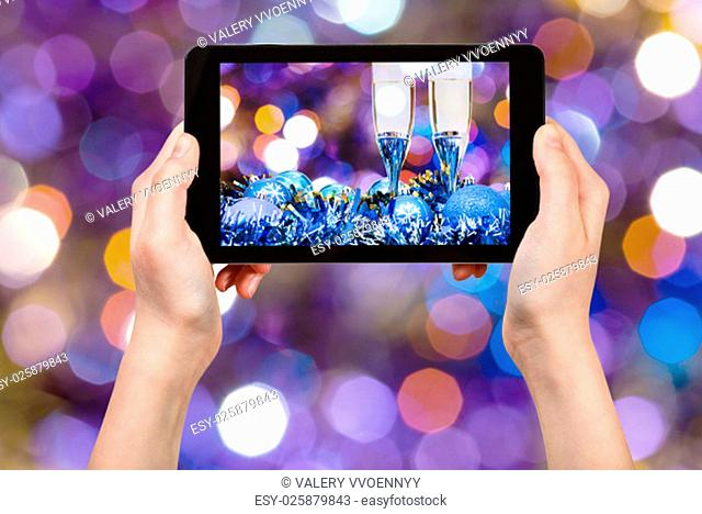 man takes photo of Christmas still life - two glasses of champagne at blue Xmas decorations with dark violet and red blurred Christmas lights bokeh background