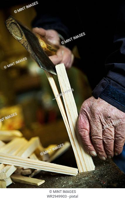 Close up of a man in a sailmaker's workshop splicing wooden pegs with a hand axe