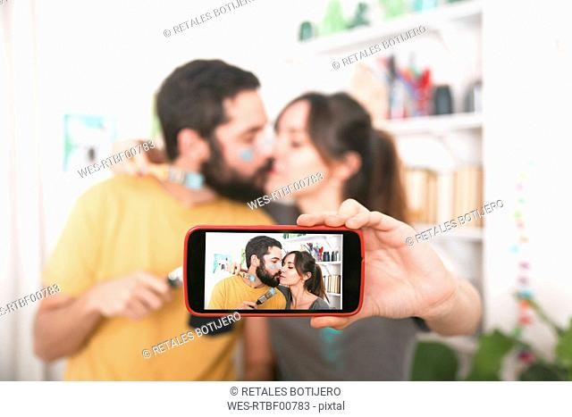 Young couple kissing and taking a selfie with paintbrushes