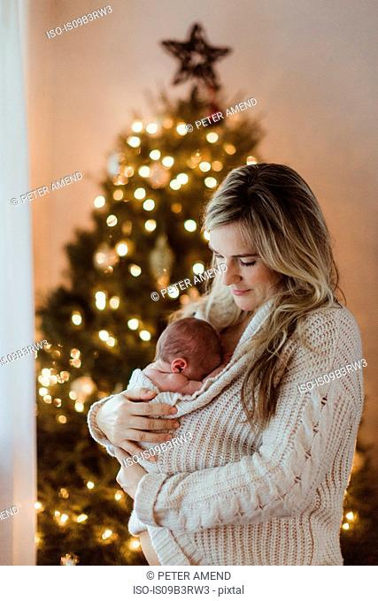 Mid adult woman cradling new born baby daughter wrapped in cardigan at Christmas